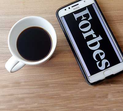 Mobile phone showing Forbes beside a coffee cup
