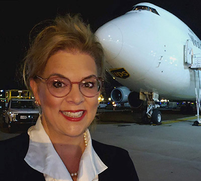 Kelly Lepley smiling in front of a plane