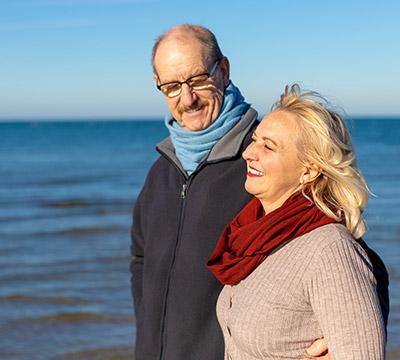 An elderly couple walking along the beach