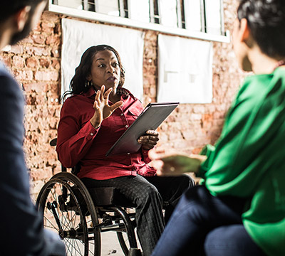 Businesswoman of color in wheelchair leading group discussion